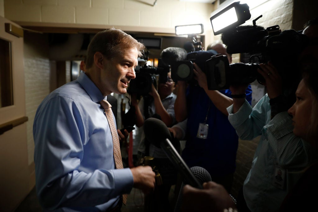 Jordan speaks to a crowd of reporters in what appears to be a basement hallway.