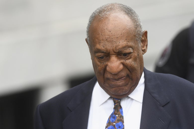 Bill Cosby, wearing a suit for his sentencing, looks downward