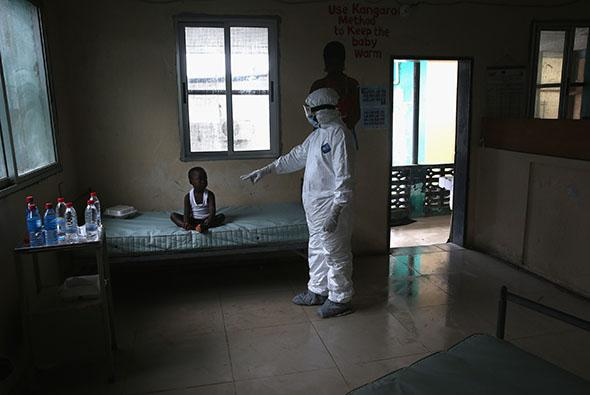 A Liberian Ministry of Health worker, dressed in an anti-contamination suit, speaks to Banu, 4, in a holding center for suspected Ebola patients.