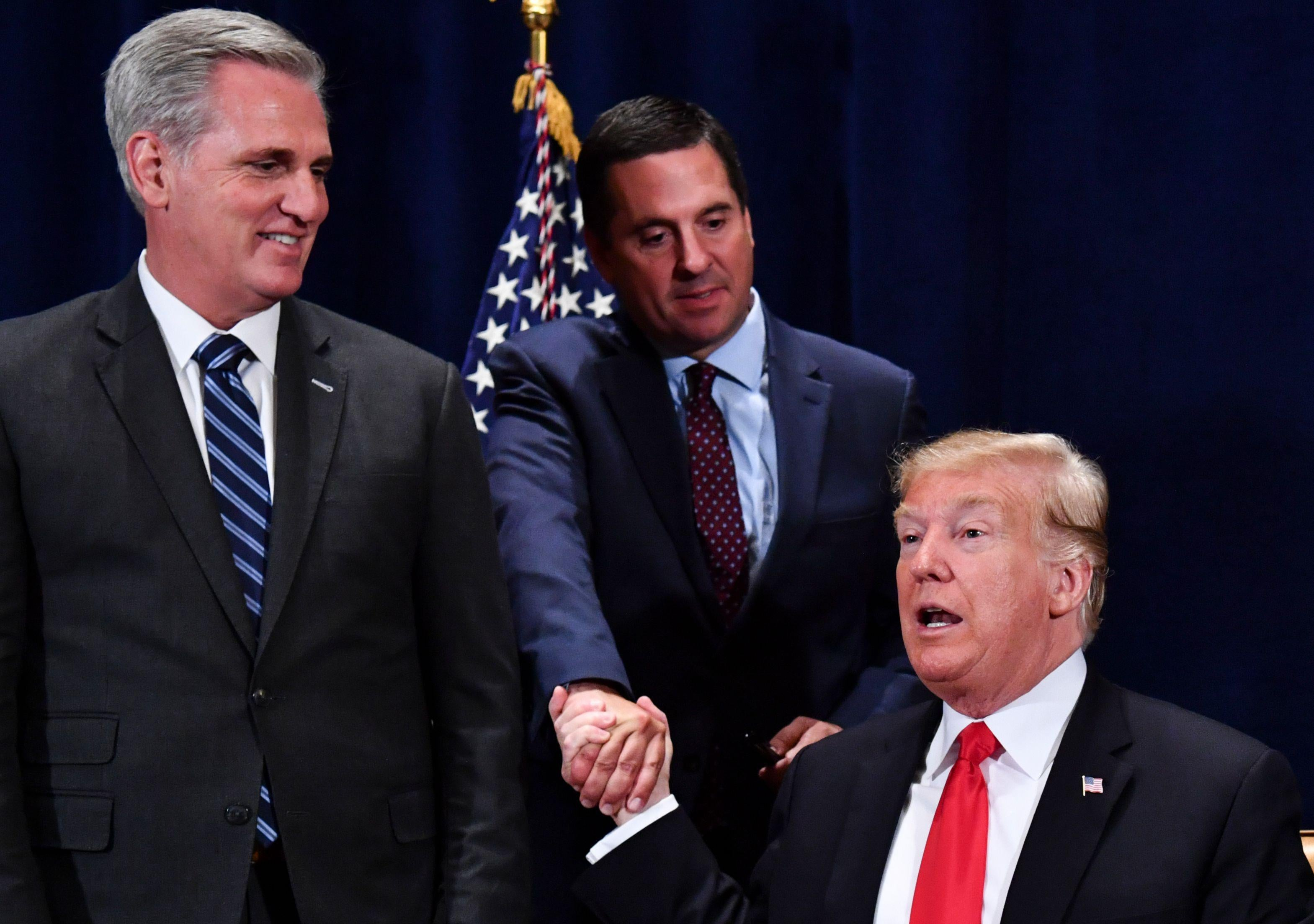 President Trump shakes hands with Rep. Devin Nunes as then-House Majority Leader Kevin McCarthy looks on Oct. 19, 2018.