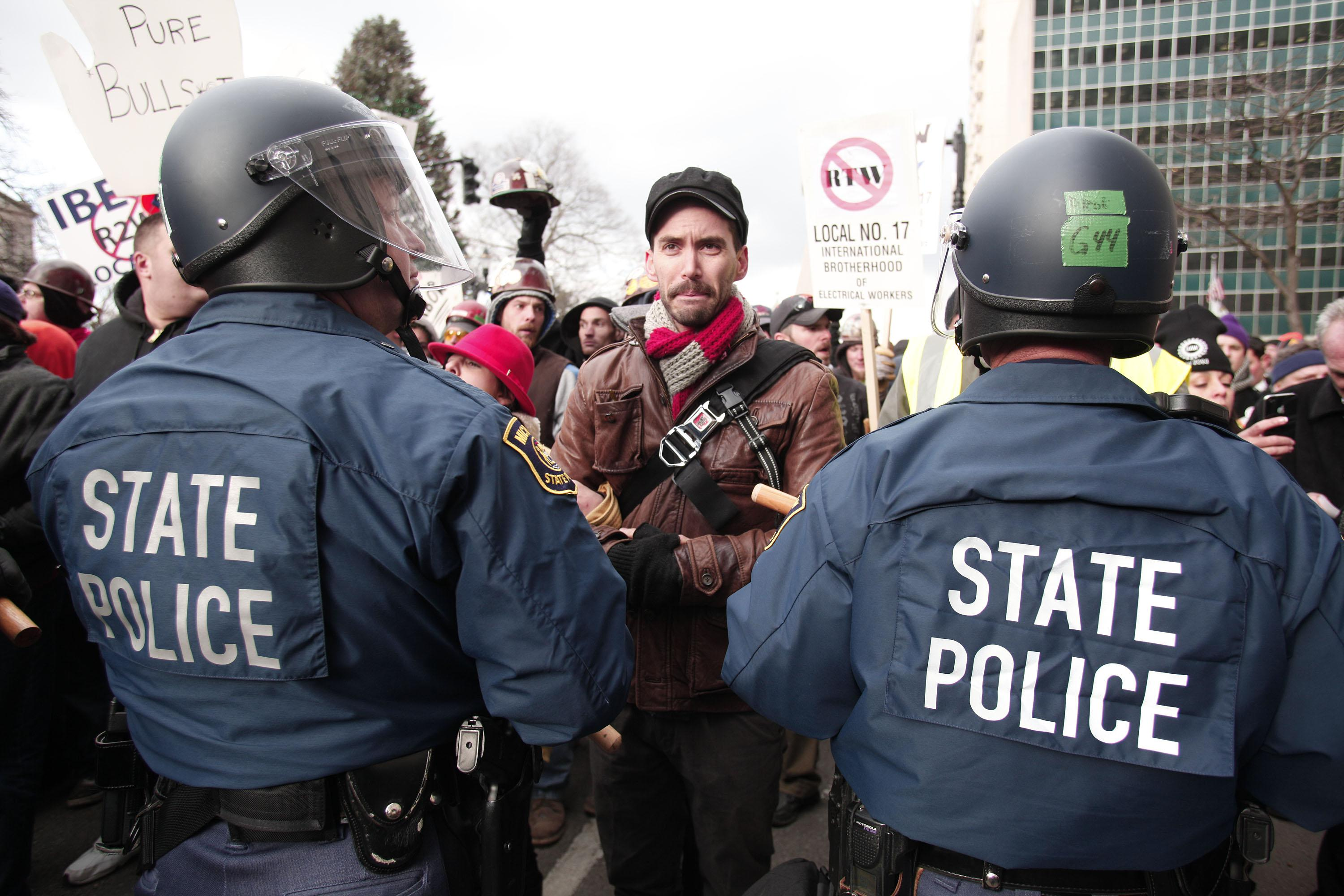 Michigan State Police in riot gear stand with batons while protestors block a street during a rally at the Michigan State Capitol to protest a vote on Right-to-Work.