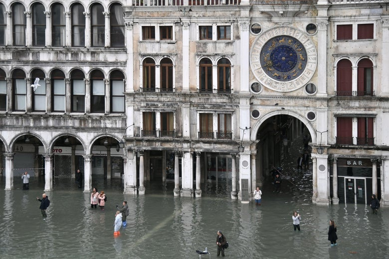 People walk across the flooded St. Mark's Square.