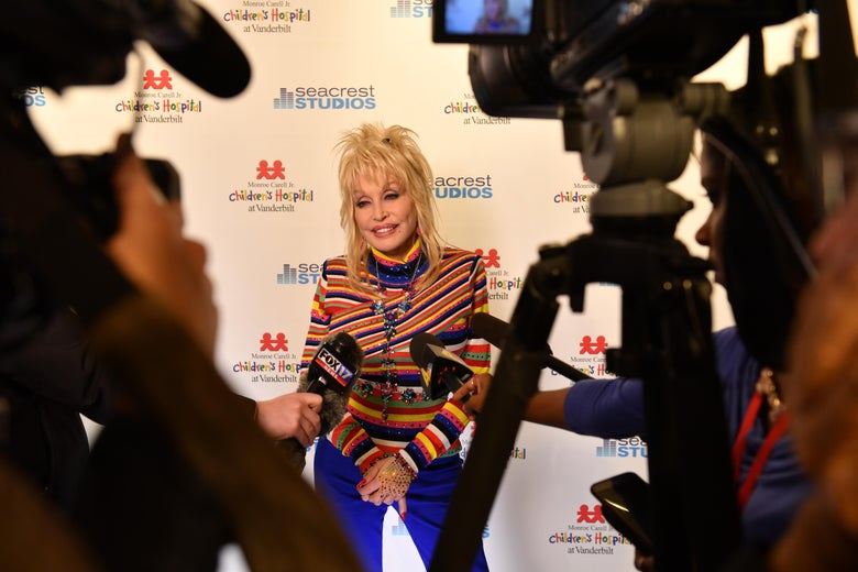 Wearing a red, orange, blue, green and white striped shirt, Dolly Parton poses with film cameras, tripods and microphones in the foreground
