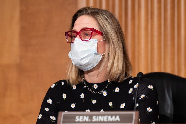 Sen. Kyrsten Sinema in a mask at a dais with a name placard in front of her