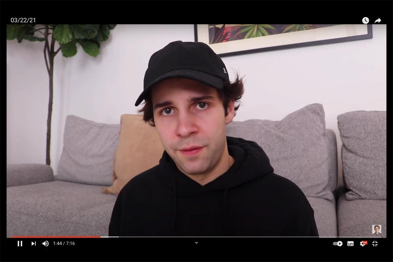 A boyish young white man stares somberly at the camera in a black hat, black hoodie, and swoopy hair.