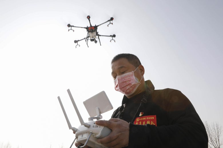 A man wearing a face mask operates a drone flying in the sky.