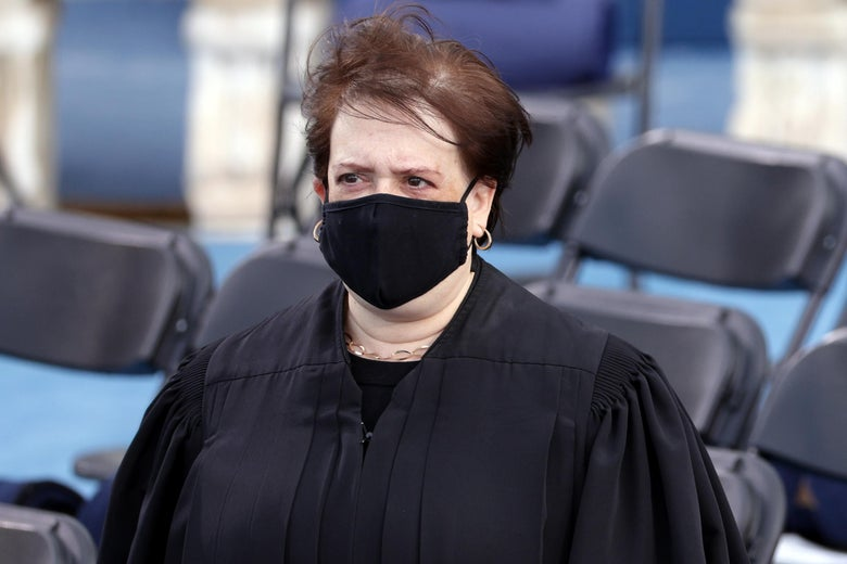 Elena Kagan stands outside wearing a robe and a mask.