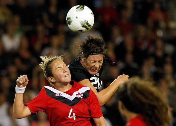 Abby Wambach #20 of the United States heads the ball against Carmelina Moscato #4 of Canada in September 2011 in Portland, Oregon.