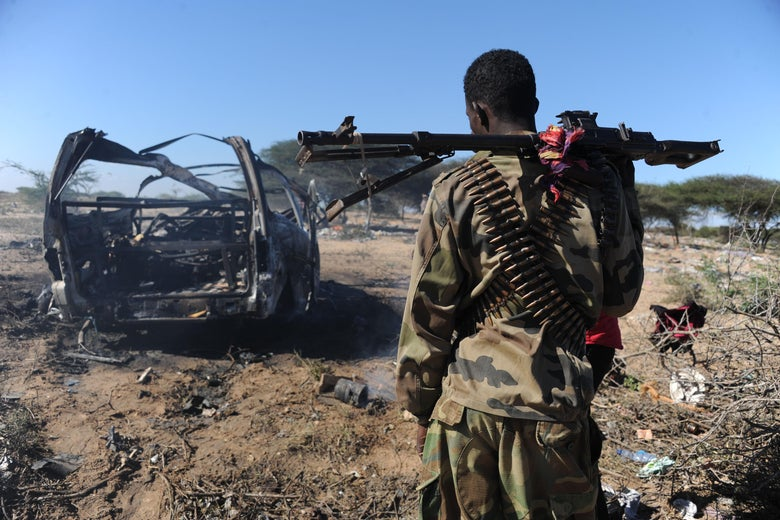 A soldiers checks the area where a suicide bomber from Somalia's Shebab insurgents killed at least 12 people and wounded 27 others, on September 8, 2014, by ramming a vehicle packed with explosives into a convoy of African Union troops in Mogadishu. The attack, the latest in a string of killings, comes exactly one week after a US airstrike killed the chief of the Al-Qaeda-linked Shebab rebels, Ahmed Abdi Godane, prompting threats of retaliation from the extremists.    AFP PHOTO MOHAMED ABDIWAHAB        (Photo credit should read Mohamed Abdiwahab/AFP via Getty Images)