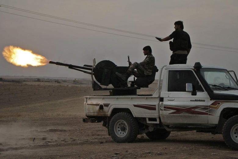 Turkish-backed Syrian fighters fire a truck mounted heavy gun near the town of Tukhar, north of Syria's northern city of Manbij, on October 14, 2019, as Turkey and it's allies continues their assault on Kurdish-held border towns in northeastern Syria.