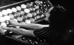 An unnamed worker attaches lids onto boxfuls of canning jars in a still image taken from the 1920s Frank Gilbreth research film.