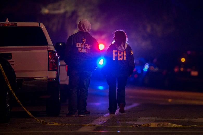 Two individuals in FBI jackets are seen walking in the glare of police lights.