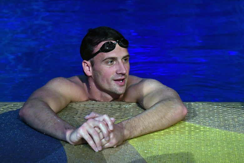 Ryan Lochte on the edge of a pool with goggles on his head