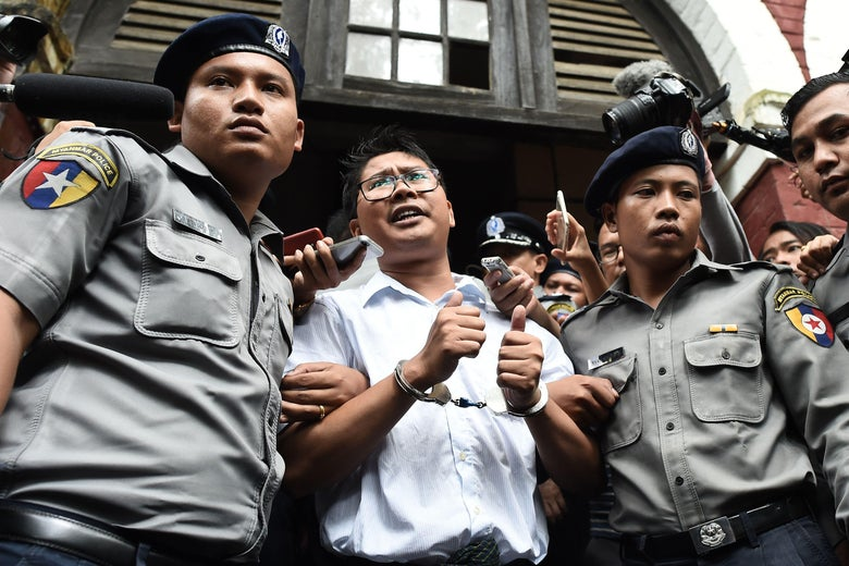 Myanmar journalist Wa Lone is escorted by police after being sentenced by a court to jail in Yangon on September 3, 2018.