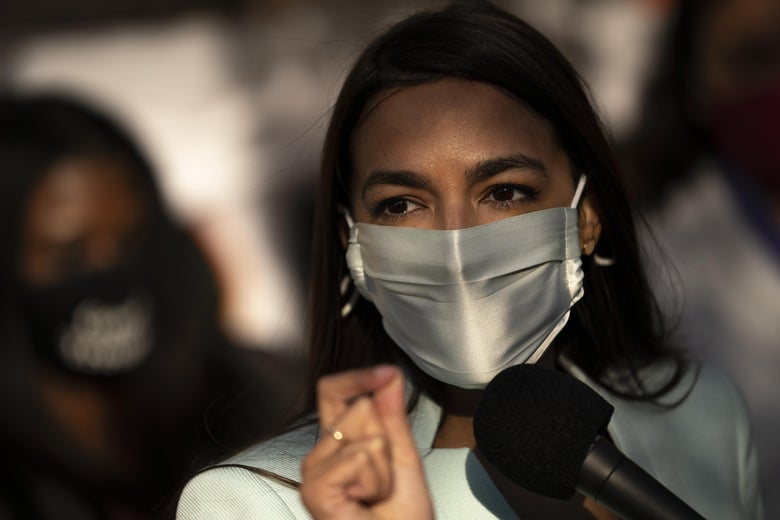 Alexandria Ocasio-Cortez speaking with a mask on at a mic outside