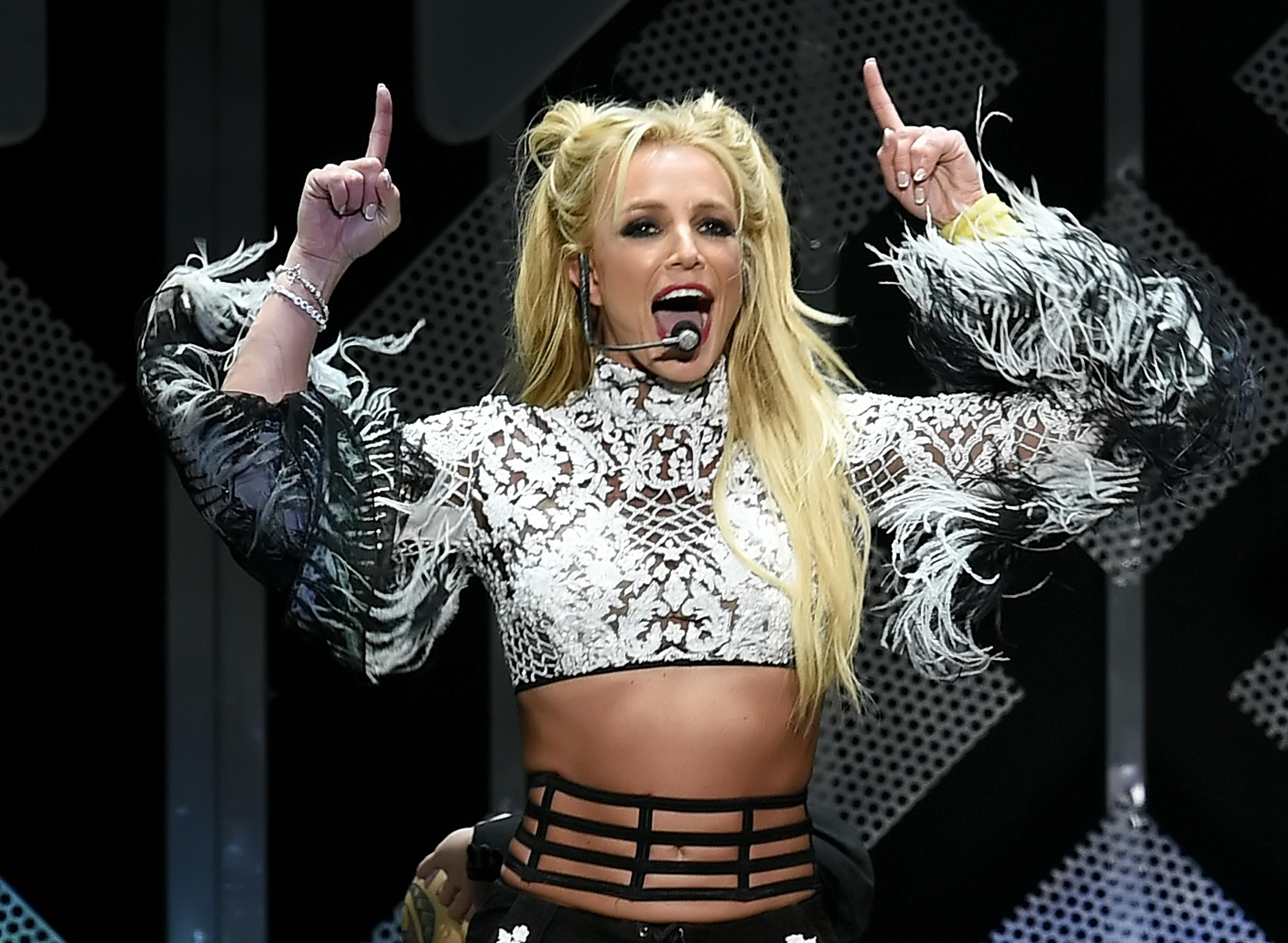 Britney Spears makes a celebratory gesture on stage.