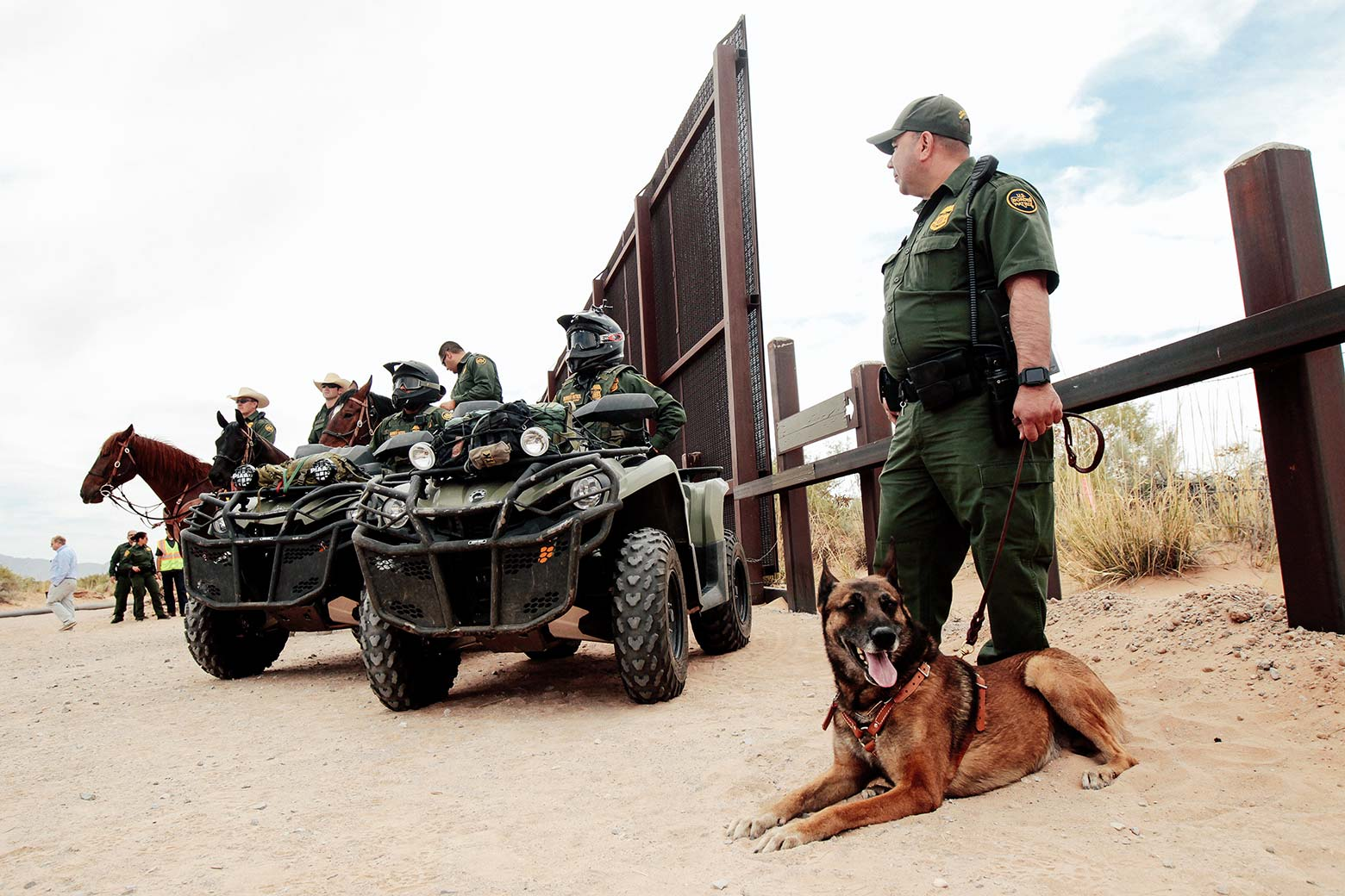 Border Patrol agents on horses and ATVs, as well as a guard on foot with a dog, at the Southern border.