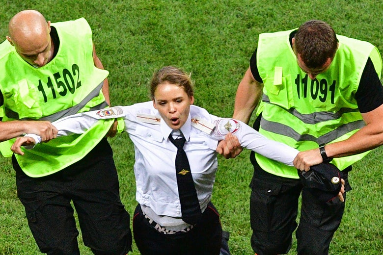 A woman in a police uniform is held on each arm by men wearing bright vests.
