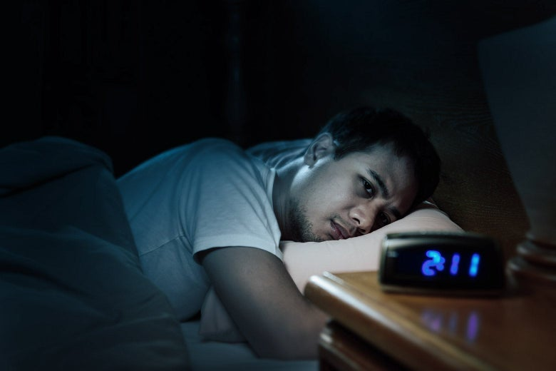 A worried man in bed looks over at the nightstand clock, which reads 2:11