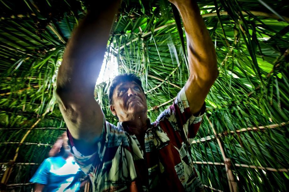 Jake Billiot, a member of the Pointe-aux-Chien tribe, works on a Palmetto hut built during a summer camp session for the tribe's children to expose them to their disappearing culture.
