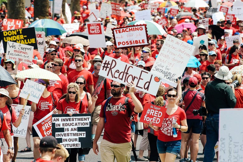Teachers dressed in red march toward the capitol with signs.