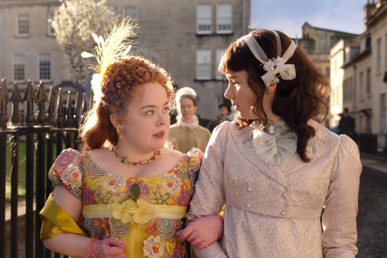 Two women in period dress link arms as they walk outside.