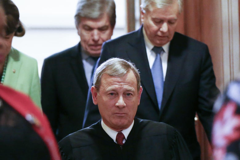 John Roberts is seen walking, followed by men in suits.
