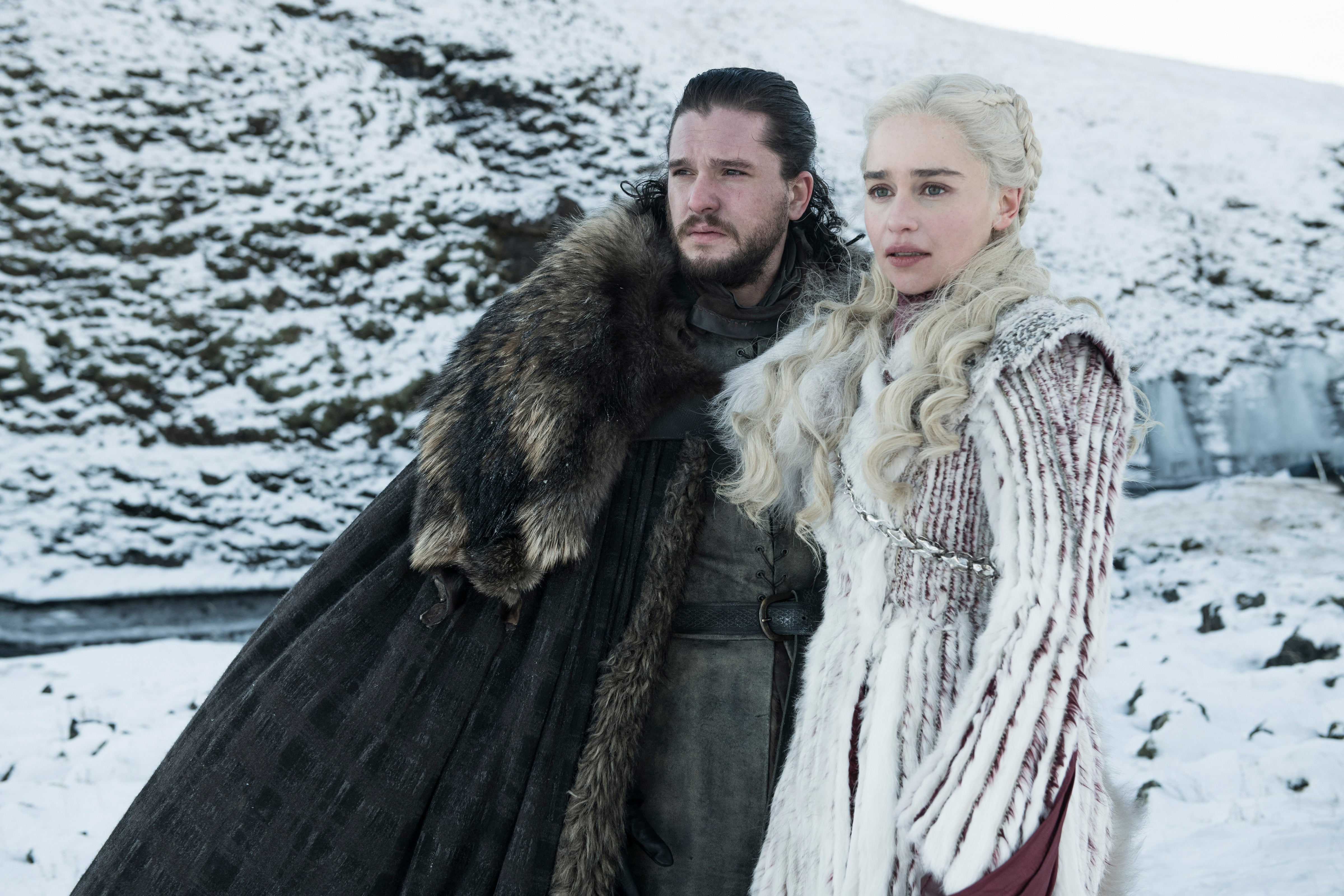 Kit Harington and Emilia Clarke stand in a snowy landscape.
