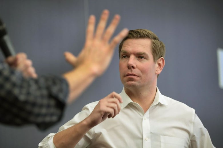 Swalwell, wearing a white button-down shirt, listens to a question.