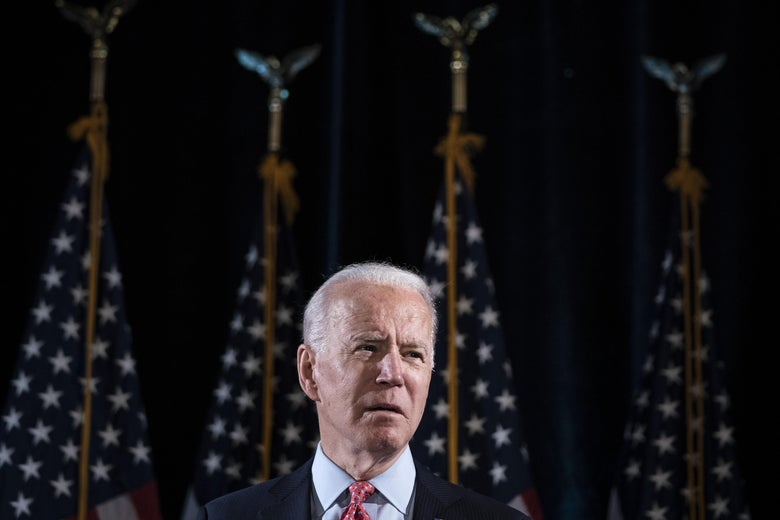 Joe Biden stands in front of four American flags.