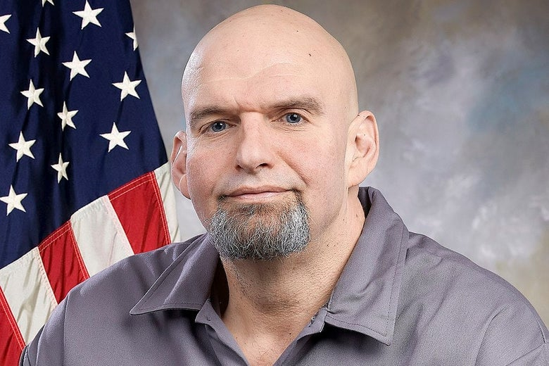 John Fetterman wearing a gray shirt, sitting in front of an American flag