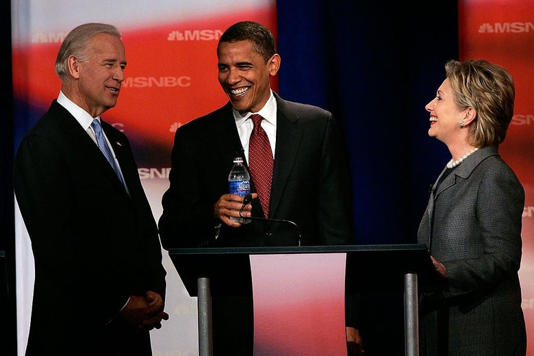 Biden and Clinton flank Obama, who is standing in front of a red lectern. The three are looking at each other and smiling.
