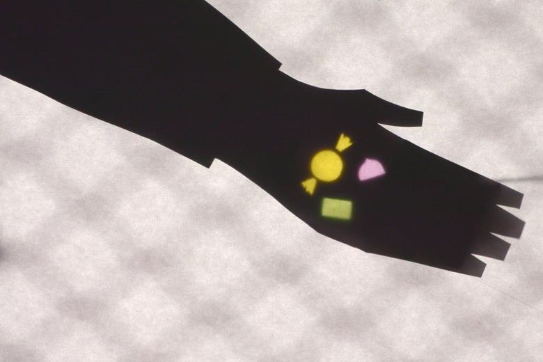 A shadow puppet hand holds out its palm with multicolored pieces of candy in it.