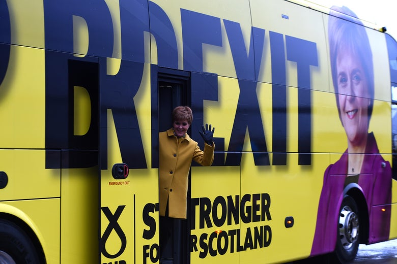 "Nicola Sturgeon leans out the door of a yellow campaign bus reading ""Stop Brexit: Stronger for Scotland."""