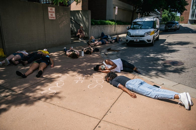 College students lying prostrate on a sidewalk in protest.