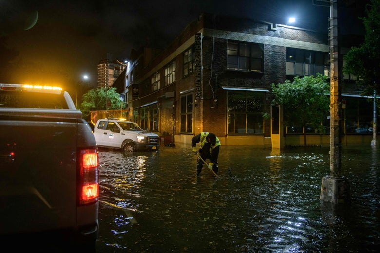 A worker unblocks drains on a street affected by floodwater in Brooklyn.