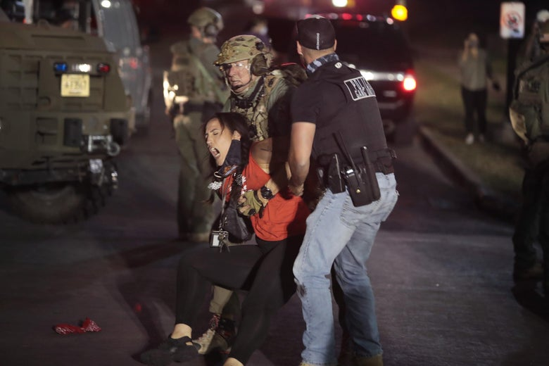A National Guardsman and a plainclothes law enforcement officer grab a screaming woman