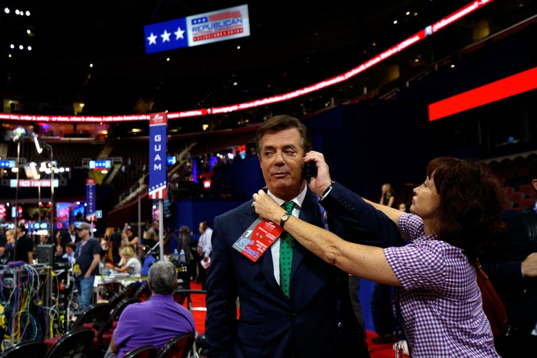 Manafort holds a cell phone to his ear as a credential is placed around his neck while he stands on the convention floor.
