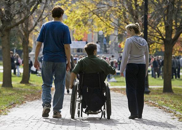 Wheelchair bound man with friends.
