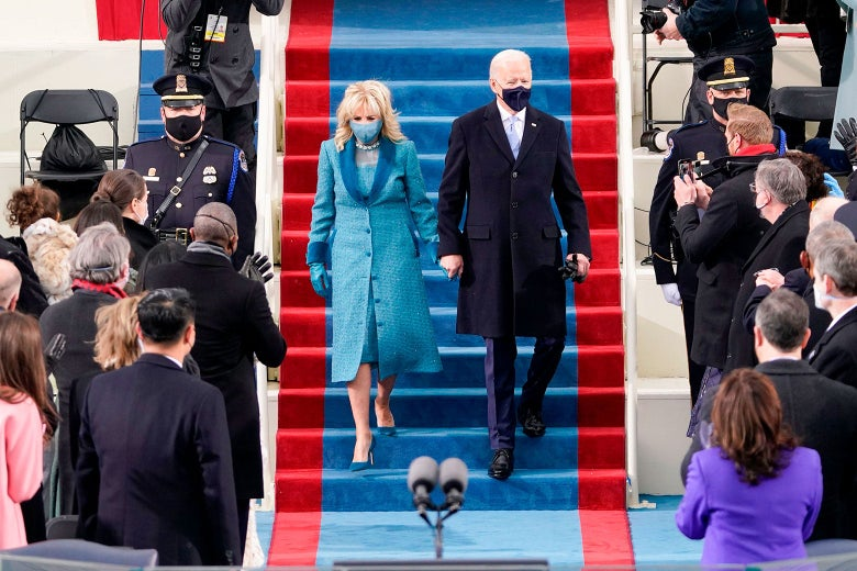 Jill and Joe walk down the stairs at inauguration. Jill wears a blue coat with a matching blue dress, mask, and gloves. Joe wears a fitted suit with an overcoat and a dark mask.