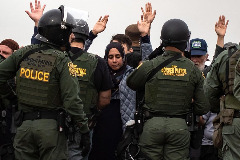 Demonstrators look down and hold their hands in the air. A line of border patrol agents in uniform stand in front of them.