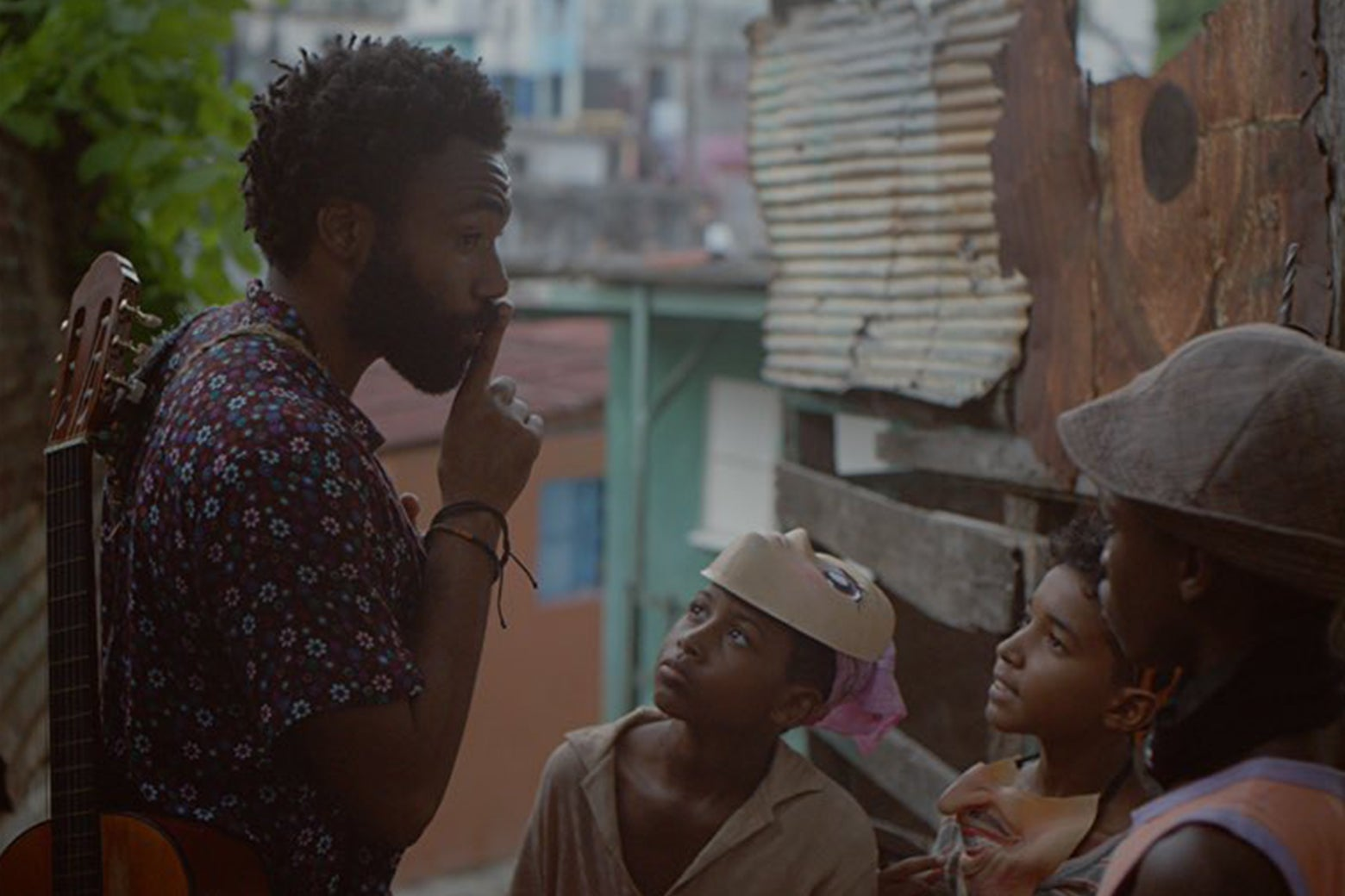 Donald Glover shushes some children in a still from Guava Island.
