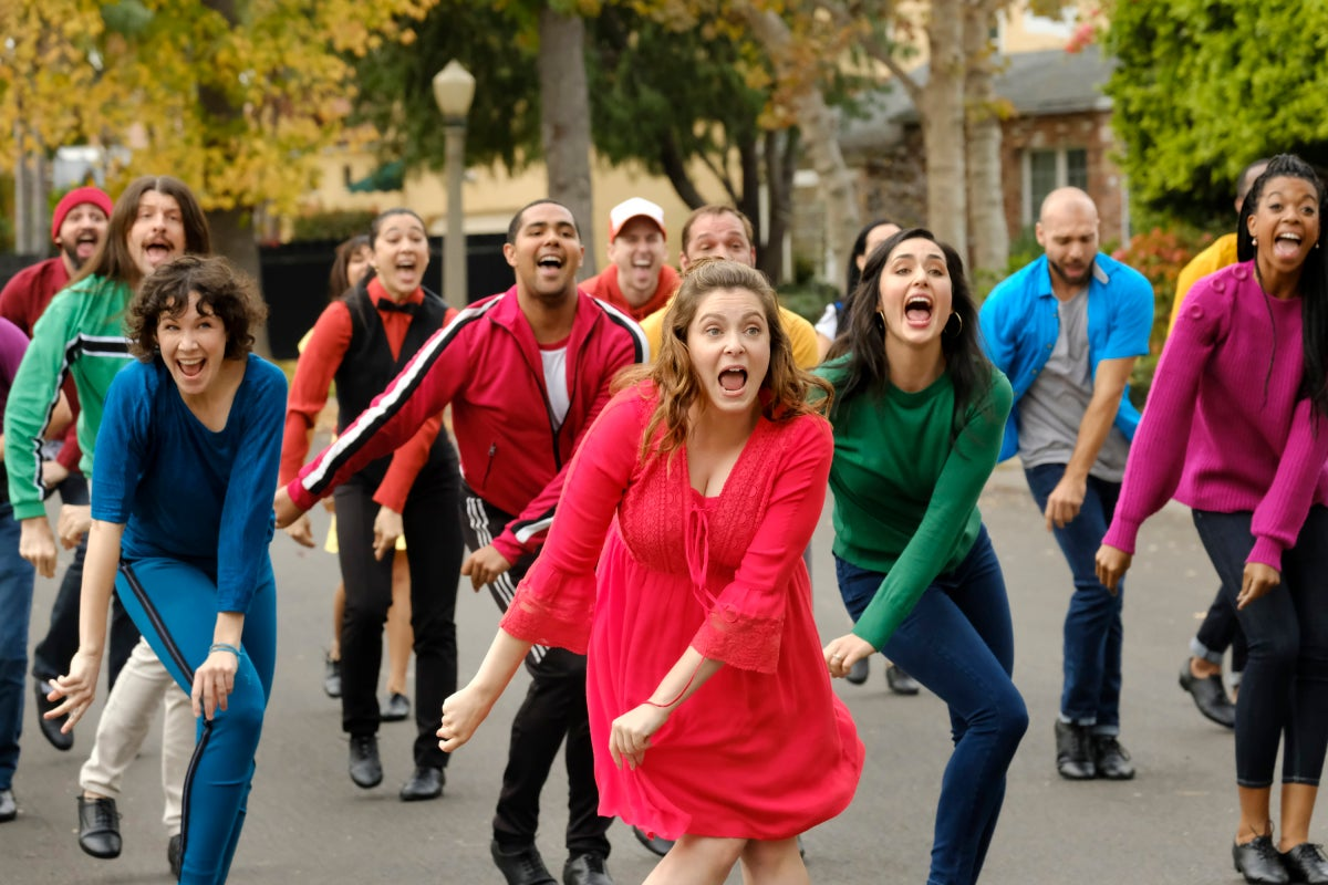 Rachel Bloom leads a crowd of people dancing in a street, all wearing bright colors.