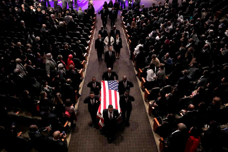 Pallbearers carry a casket with an American flag on it.