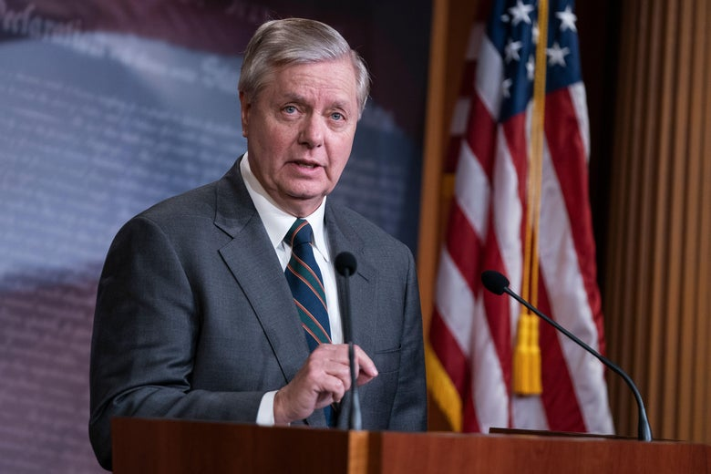 Lindsey Graham speaks at a podium with an American flag in the background