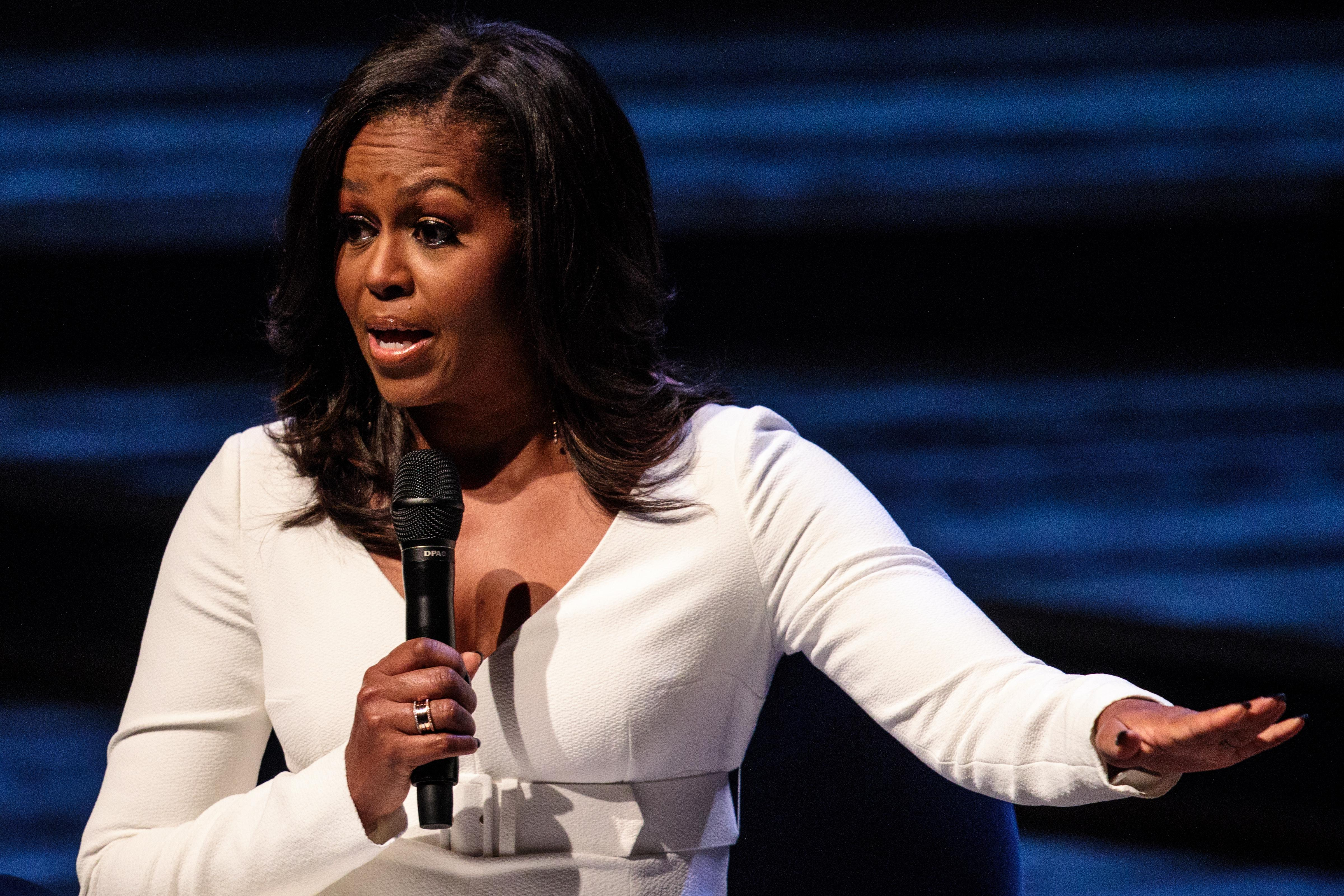Former U.S. First Lady Michelle Obama speaks onstage, wearing a white pantsuit