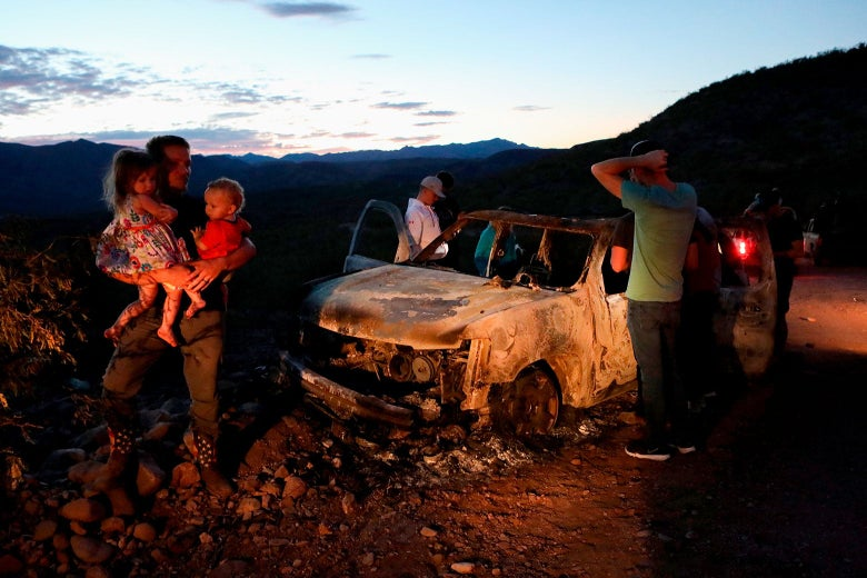On Tuesday, members of the LeBaron family look at the car where some of the nine murdered family members were killed and burned earlier that week in Mexico.