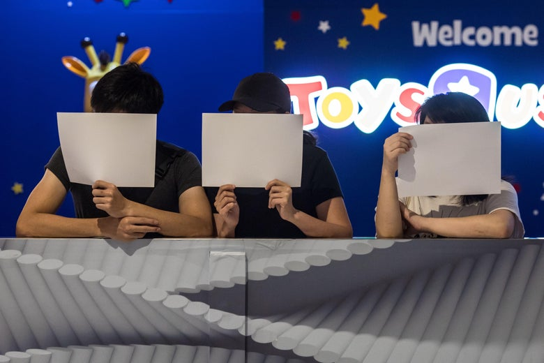 Three protesters hold up white pieces of paper in front of their faces while standing in front of a Toys 'R' Us.
