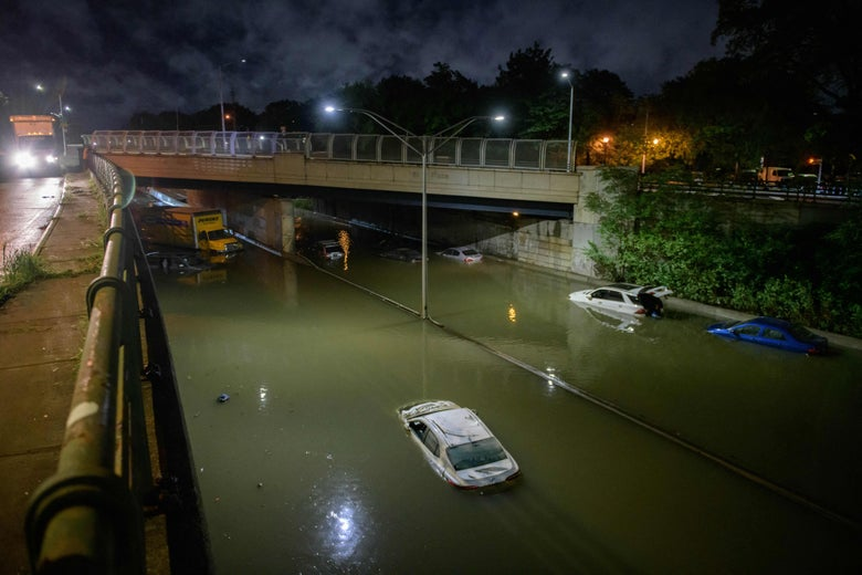 Floodwater surrounds vehicles following heavy rain on an expressway in Brooklyn.