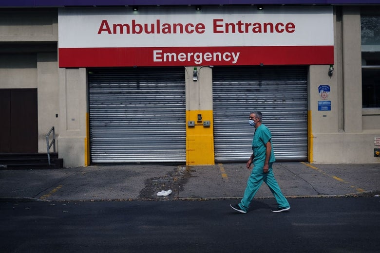 """A man with short graying hair walks past a pair of garage doors below a sign that reads """"Ambulance Entrance, Emergency."""""""